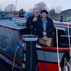 "Mr Jones and his wife on board their canal boat ""Nauti Buoy""."